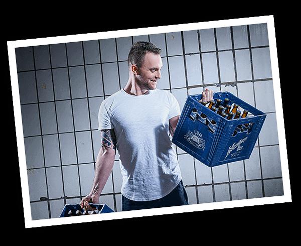 Junger kräftiger Mann stemmt Wieselburger Bierkiste